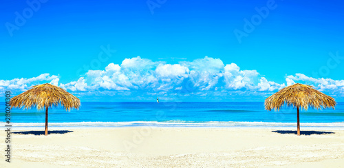 Foto auf Leinwand Blau Straw umbrellas on empty seaside beach in Varadero, Cuba. Amazing blue sky with clouds. Relaxation, vacation idyllic background. Free space. Banner design mockup