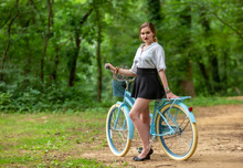 Girl In A Skirt With A Bike In...