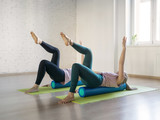 Two caucasian women doing pilates with foam rollers, in fitness studio, selective focus.
