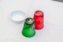 Green And Red Water Glasses And White Ashtray On A Table