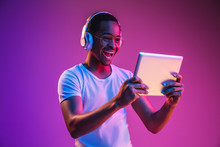 Young African-american Man's Listening To Music In Headphones, Using Tablet In Neon Light On Gradient Background. Concept Of Human Emotions, Facial Expression, Summer Holidays Or Weekend, Hobby,