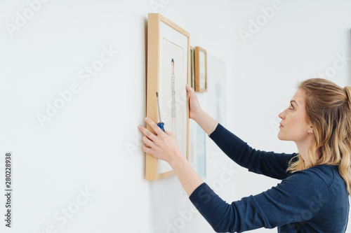 Young woman hanging a picture on a wall Fotobehang