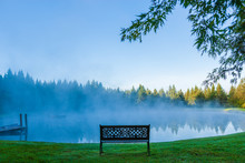 A Decorative Bench In Front Of A Foggy Pond, Stowe Vermont, USA