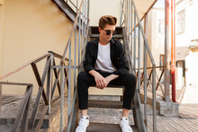 Modern Young Hipster Man In Trendy Sunglasses In Stylish Black Shirt In A T-shirt In Elegant Striped Pants In Sneakers Sits On An Iron Old Staircase In The Street. Cool Guy Is Resting In The City.