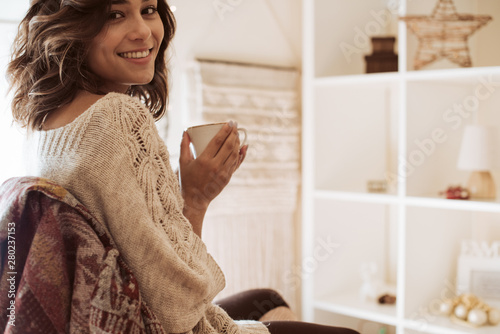 Woman drinking a cup of tea at home - Christmas Canvas-taulu