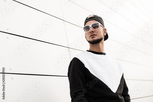 Vászonkép  Nice urban young hipster man in stylish sweatshirt in black trendy black baseball cap in sunglasses in the city