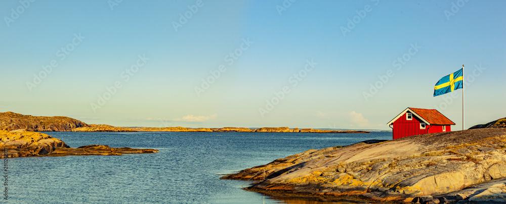 Fototapety, obrazy: Rotes Haus in Schweden an der Schärenküste mit Flagge