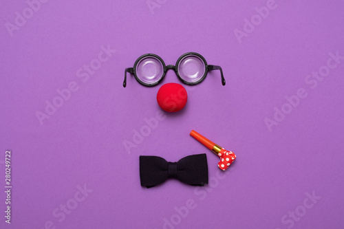 фотография Funny glasses, red clown nose and tie lie on a colored background, like a face