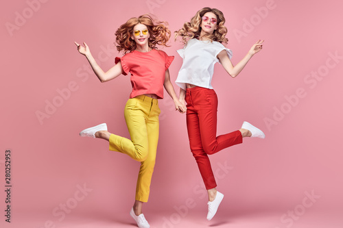 Photo  Two fashionable girl jump Smiling in colorful outfit on pink
