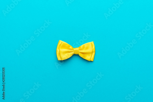 Fotomural Minimalist flat lay photo of yellow satin bow tie over turquoise blue background and copy space