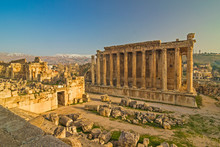 Lebanon - Baalbek (Heliopolis) - Massive Ruins Of The Temple Of Bacchus And The Part Of The Temple Of Jupiter In An Impressive Ancient Archeological Temple Complex With Snow Capped Peaks In A Far