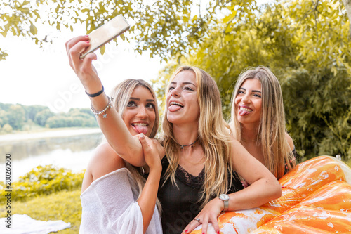 Photo female millennial girlfriends taking a selfie outdoors on the river