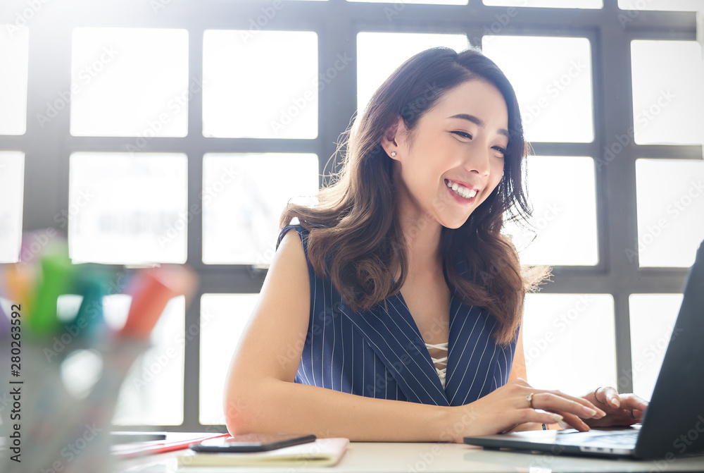 Fototapeta Portrait of smiling beautiful business asian woman with suit working in office desk using computer with copy space. Business people employee freelance online marketing e-commerce telemarketing concept