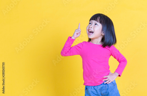 Fotografia  Portrait of young little asian girl hand point up isolated on yellow background with copy space
