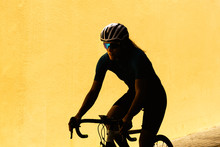 Minimalistic Silhouette Of A Female Cyclist Against Plain Yellow Wall