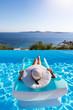 canvas print picture - Sommerurlaubs Konzept: Unbekannte Frau mit weißem Hut entspannt in einem Pool auf einer Luftmatratze und genießt die Aussicht auf das Meer