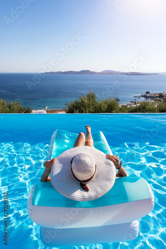 Fototapeta  Sommerurlaubs Konzept: Unbekannte Frau mit weißem Hut entspannt in einem Pool au