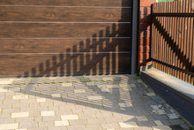 Brown Wooden Vertical Fence Near The Garage With A Gate