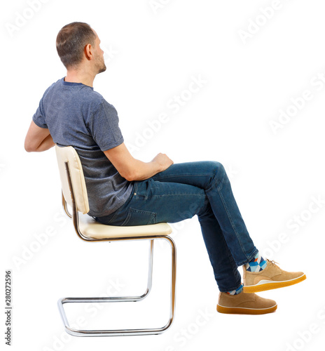 Fototapeta Side view of a man sitting on a chair. obraz