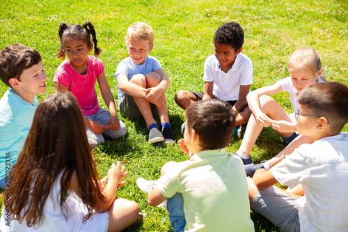 Fotografija  Group of elementary school children chatting on the green lawn