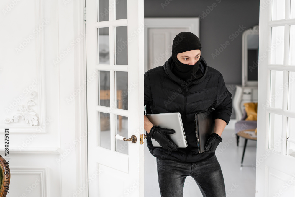 Fototapeta Thief with black balaclava stealing two modern expensive laptops. The burglar commits a crime in Luxury apartment with stucco.