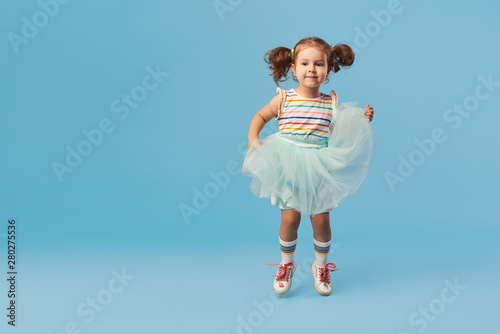 Little happy toddler child girl dreams of becoming ballerina in a cyan tutu skirt Wallpaper Mural
