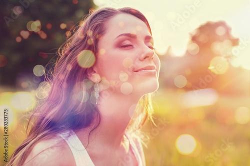 Valokuva  Young woman on field under sunset light