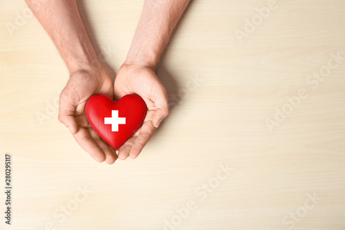 Cuadros en Lienzo  Man holding red heart on light wooden background, top view with space for text