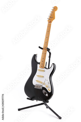 Photo  Vintage black and white electric guitar on a stand isolated on white