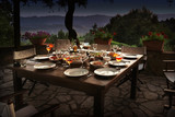 large rustic table on a garden terrace prepared for a dinner party at night