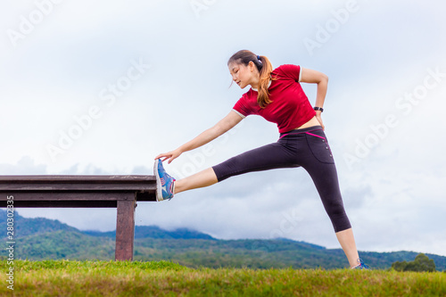 Tuinposter Voetbal Beautiful young Asian woman stretching during her morning exercise at a park on a cloudy sky day, with mouintains and sky background, healthy lifestyle, copy space