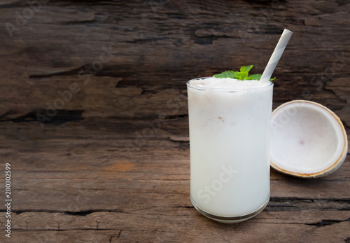 Coconut smoothies white fruit juice milkshake blend beverage healthy high protein the taste yummy In glass drink episode morning on a wooden background.