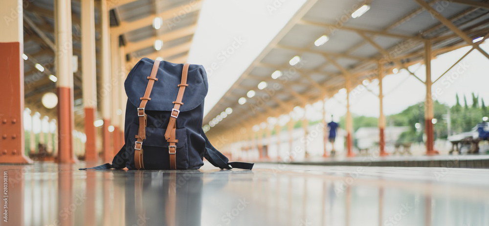 Fototapeta Backpacks on the floor at train station and copy space