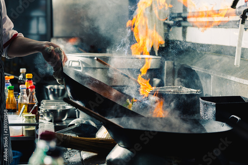 Chef stir fry in wok Wallpaper Mural