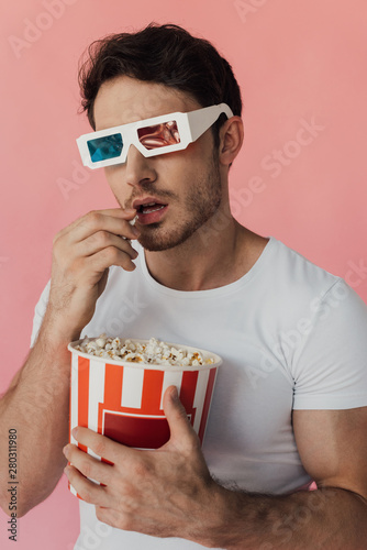 Obraz na plátně curious muscular man in 3d glasses eating popcorn isolated on pink