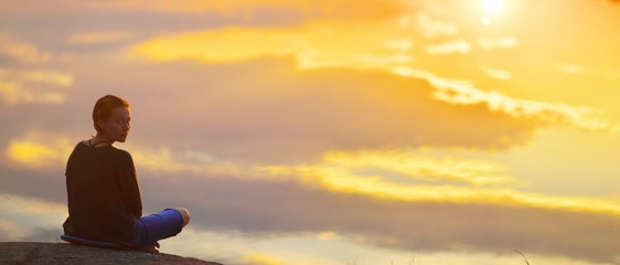 Young woman sitting enjoying peaceful moment of beautiful colorful sunset. In reflection of the lake water sees clouds and sun. Concepts of wellness happiness, peace freedom, inner mind meditating.