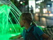 Leinwanddruck Bild - Girl at the fountain in the city at night in neon light.