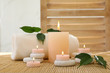 canvas print picture - Composition of spa stones, towel and burning candles on bamboo mat
