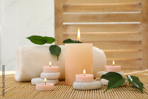 Composition of spa stones, towel and burning candles on bamboo mat Wallpaper Mural