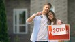 Happy family couple smiling, holding house keys standing near sold signboard
