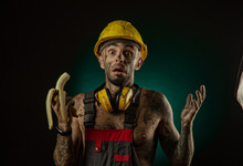Portrait Of A Happy Smiling Miner Eating A Banana For Lunch