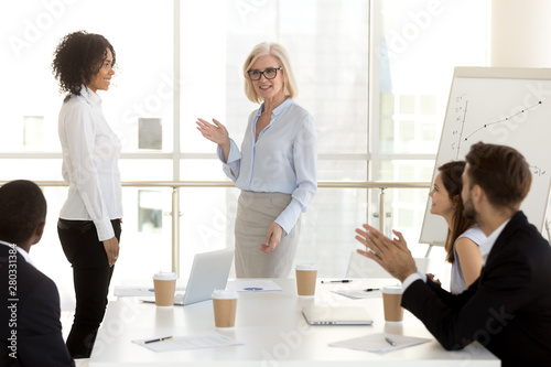 Mature businesswoman introducing new worker to colleagues