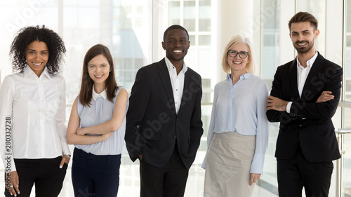 Portrait of diverse smiling team employees standing in row in office