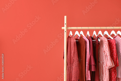 Valokuva  Rack with hanging clothes on color background
