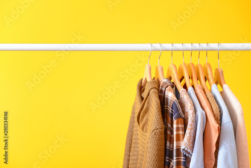 Rack with hanging clothes on color background Wallpaper Mural