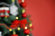 Blurred view of beautiful Christmas tree on color background, closeup