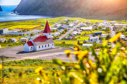 Beautiful view of Vikurkirkja christian church in blooming flowers