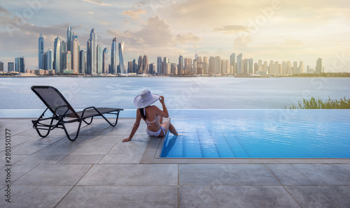 Foto Beautiful panorama of Dubai Marina skyline in a background with a pool, deck chair and woman with a white hat at sunset
