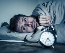 Young Man In Bed With Alarm Clock Feeling Desperate And Distress Not Able To Sleep With Insomnia