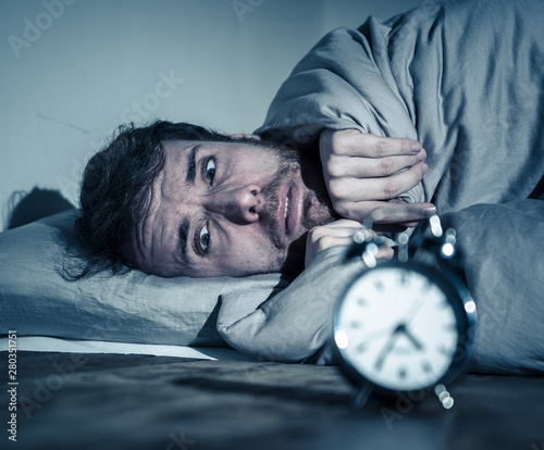 Young man in bed with alarm clock feeling desperate and distress not able to sle Canvas Print